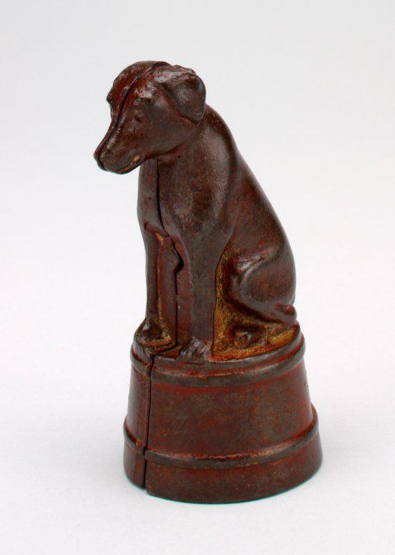 metal dog seated on a red drum-shaped platform; coin slot on back of dog; short tail; floppy ears; made in 2 parts held together by a screw