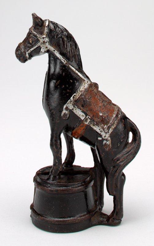black horse standing on platform; silver trim on saddle bridle; red pigment traces on saddle; coin slot in platform; coin slot in back of neck