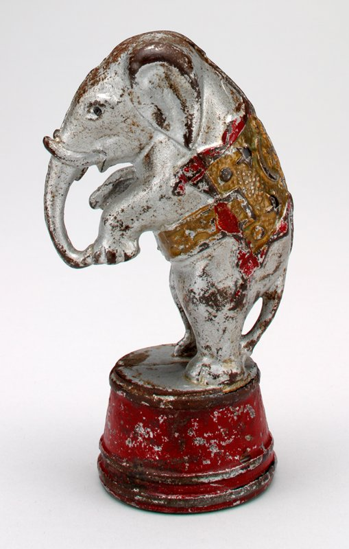 silver elephant standing on hind legs on red drum; wearing red and gold pad on back; coin slot top of head