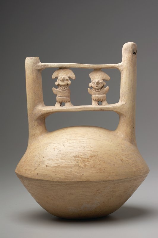double spouted vessel with bridge between spouts on which stand two small figures; white pottery