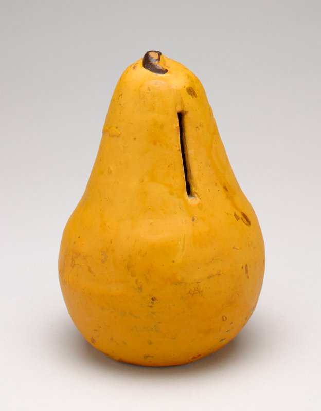ceramic bank shaped and painted to resemble a yellow pear with brown stem; coin slot in neck of pear