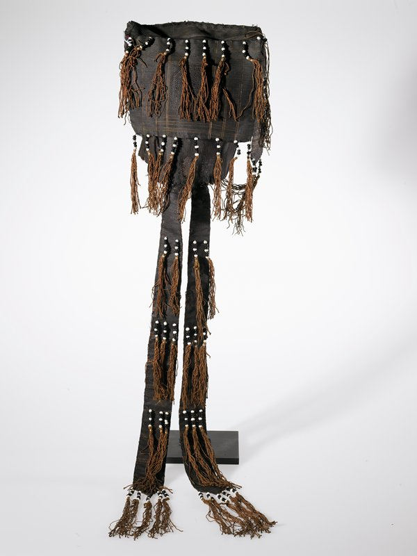 dark brown with light brown stripe details and tassels; top flap with tassels; strip with beads and tassels on each side, two long strips on back; long flap with tassels at top and bottom on back; black and white beads