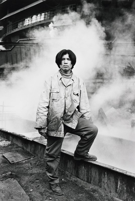 young man wearing a dirty smock, turtleneck, gloves, pants and boots, with his PL foot on a steel beam; clouds of smoke behind man