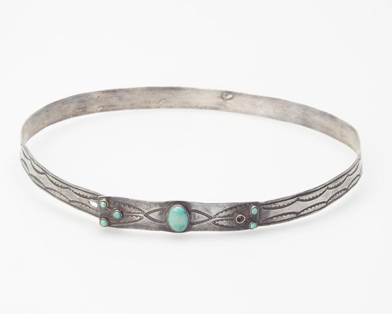 silver band, adjustable, with stamped design; design of 1 large turquoise and 6 small ones; 1 stone missing; traces of foreign matter