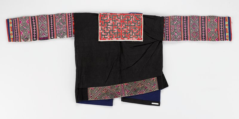 """open front with embroidery on 12-1/2"""" lapels; dark blue indigo; sleeves have solid strips of applique with scroll, floral and geometric embroidery in pink and grey; back """"sailor"""" collar, 6-1/4"""" x 10"""", in labyrinth applique patterns in red, black, pink; 3"""" scroll embroidered band on bottom back edge; blue lining"""