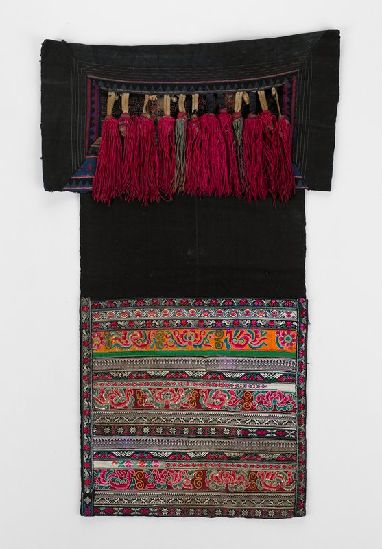 lined upper rectangular black panel; geometric embroidery and applied tape; 12 long/large tassels, red and green, suspended by knotted tape; lower panel of horizontal bands of scroll embroidery and tapes--reds, orange, blues, greens, white and black