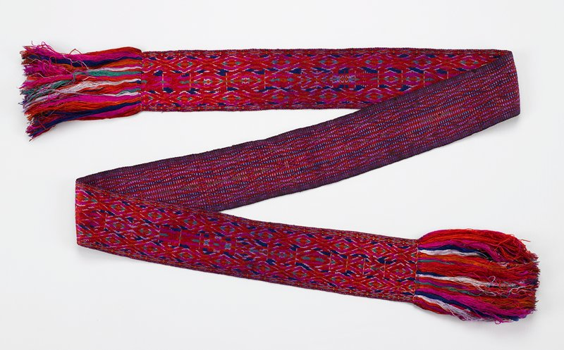 geometric embroidery with borders; red, magenta, orange, blue, white, green; self fringe with additional fringe added on each end; heavy fringe