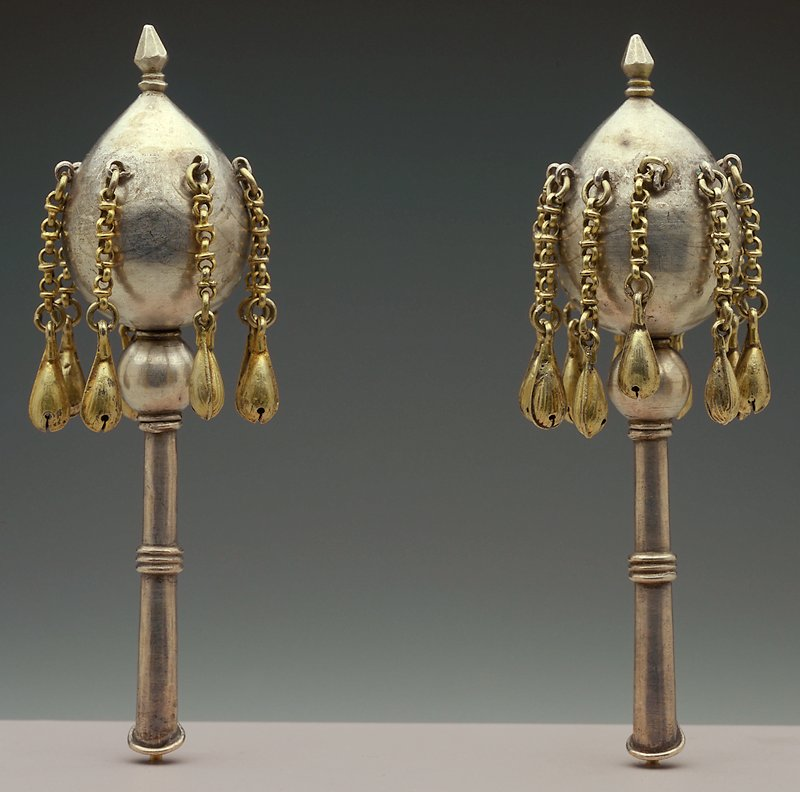 egg-shaped upper section, pointed on top with pointed finial, with teardrop shaped gilt bells attached to short chains at top of egg; handle with sphere under egg and two sets of rings