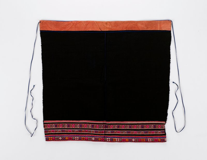 black square shape with long string ties; reversible; one side has rows of cross stitch embroidery on bottom in pink and purple, primarily, with metal accents; other side has silk applique bands in red, green and pink on bottom and cotton applique bands in red and blue at top