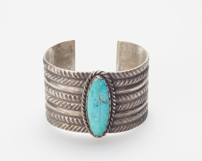 3 double rows of filed design separated by plain silver bands; large turquoise with scalloped bezel surrounded by twisted wire