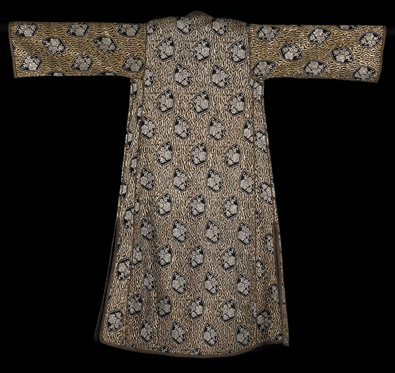 """black with overall silver and gold metallic jacquard woven floral designs separated by thick, wavy lines, also in silver and gold metallic jacquard patterning; black and gold hand-applied corded edges opening with same thread; buttons down PR; narrower cording surrounds sleeve edges; 20"""" slits at sides; completely line in a black lining fabric"""