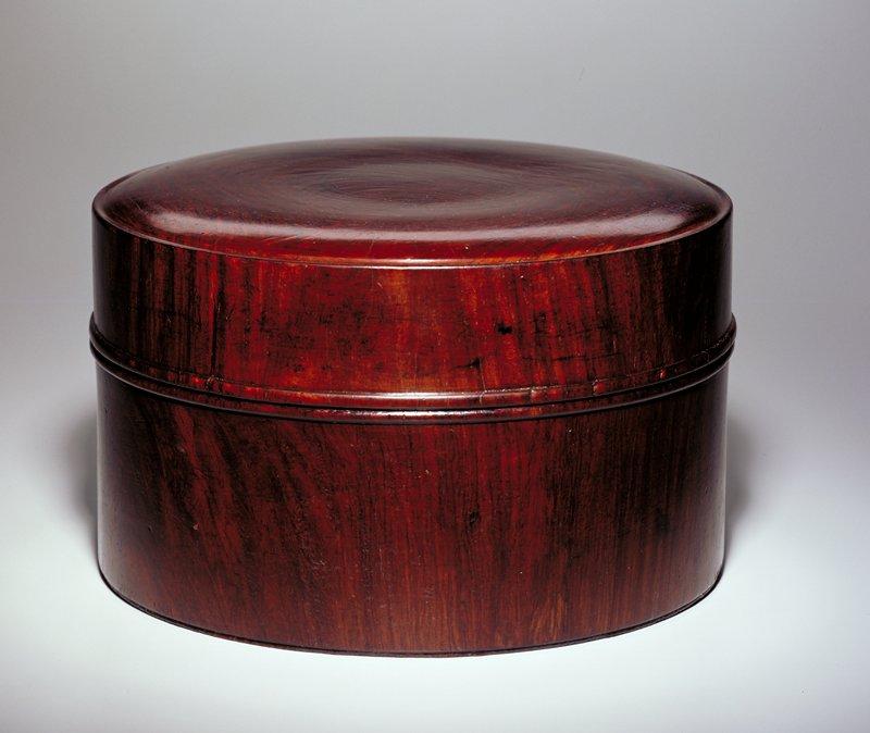 round dark-brown wood covered box