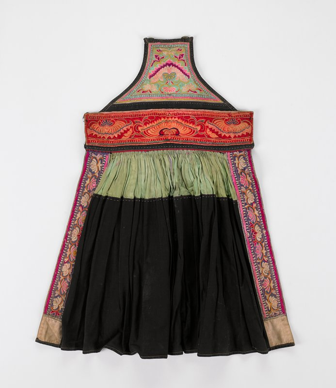 bib and waist band totally embroidered in abstract floral design; bib in light green with pink; waist band in orange and red; skirt part shirred green with black; skirt bound on sides with flower embroidered on purple tape; patched-up neck loop; woven tied with tassels; apron bib lined in batik; blue and printed fabric
