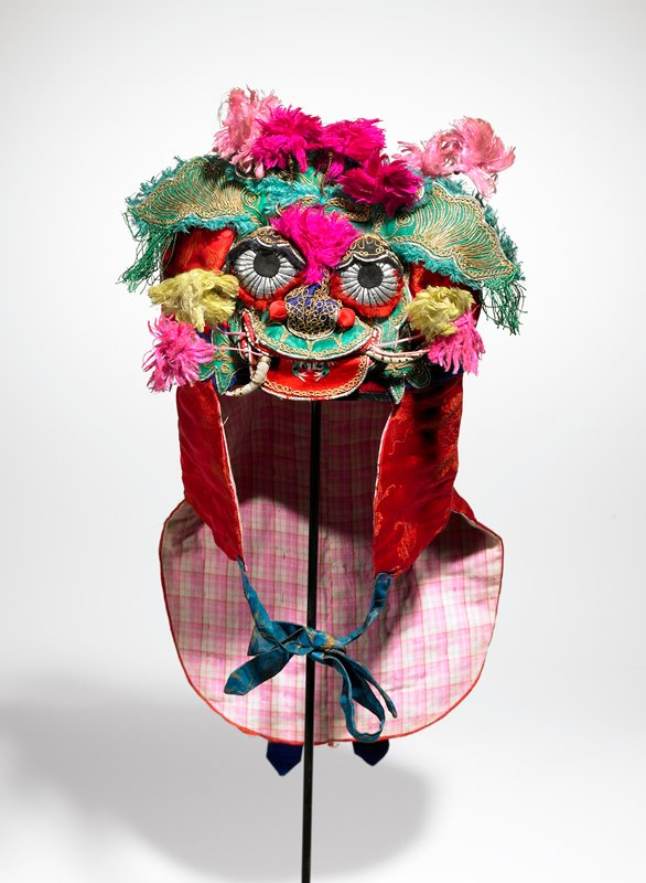 red, green, pink; three dimensional animal-like face with white tusks, red and green mouth, blue nose, silver paper eyes, black lids; embroidered and outlines with yellow metal thread and silver paper; pink and yellow pompoms on top and face attached with wire and springs; red brocade cape-effect with blue streamers and ties; green fringe on brow; green frog embroidered on red tongue; springs topped with dark metal bead; pink plaid lining