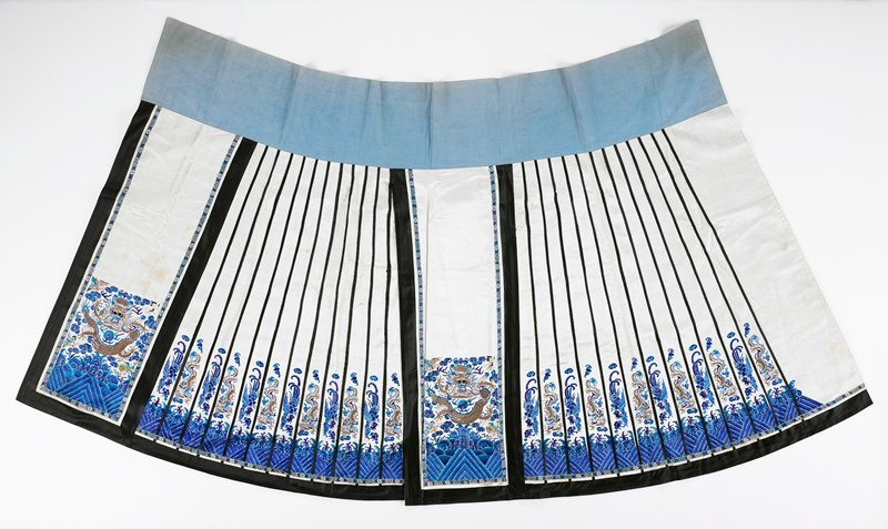 two panel lined skirt with wide light blue waistband; warp style with two wide embroidered dragon panels in elaborate designs in metal and blue silk threads on white satin ground; four small embroidered birds in corners; black border on side and lower edges; 24 narrow white bands separated by black strips with elaborate alternating bird and dragon embroidery in shades of blue and metallic threads