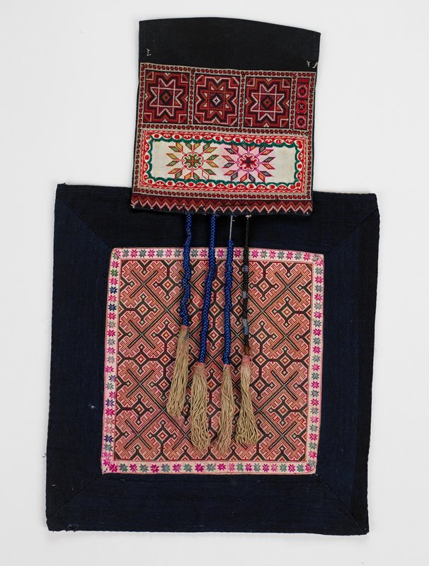 indigo with red, white, green embroidered panels; small; fringe hangs from center has 3 blue strands, 2 grey strands and 1 black strand; large square has floral and diamond shape cross stitch with indigo borders; small square has top, solid black panel