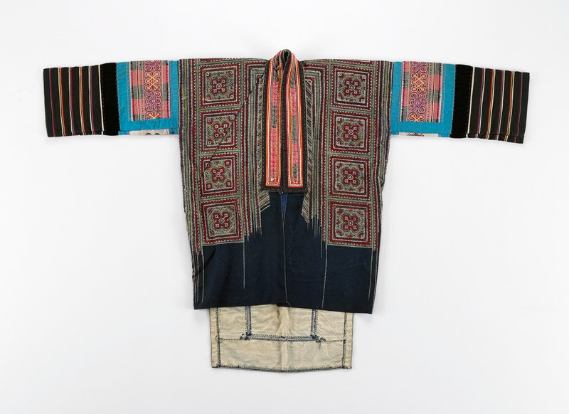 blue lined jacket; front and back in geometric patterned batik in red, white, yellow; lower portion of front is not batiked; wide neckband; tape in embroidery and appliqued design in red, black, white; back has wide tail piece with geometric cross stitch embroidery in red, yellow, white; lined sleeves have upper blue-bordered embroidered section in purple, red, yellow, black; lower sleeves have seven horizontal black bands with colored, narrow applique bands
