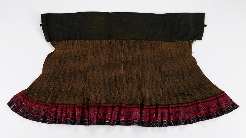 "tight accordian pleated skirt with wide (7"") dark waistband with two loops; brown damask body with 5"" applied embroidered lower border; border has four sections of alternating embroidery and ribbon tape in dark colors of red and black"