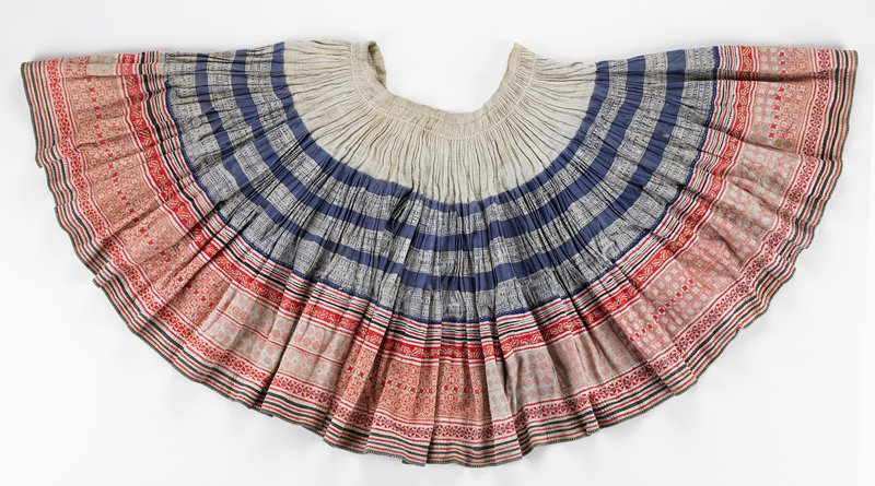 "wrap skirt in 3 horizontal sections; narrow waistband and top pleated, 5 1/4"" section in beige; center section of blue and white batik print (8""); lower band (10"") is lined and heavily embroidered in pinks, reds, ecru, and purple with appliqued red, black and white tape above and below embroidery"
