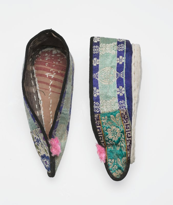 lined slipper style with pink tuffted ball at toe; silk patterned tape in green, blue and white; inner toes patched in different fabric; batik binding at ankle edge and toe; white cotton stiff stitched sole in pear shape; tied together