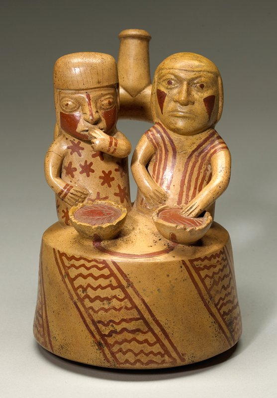 """two figures seated on round body of vessel with plates of food in front of them; spouts protrude from backs of both figures and joins in a """"U"""" shape; beige with maroon highlights"""