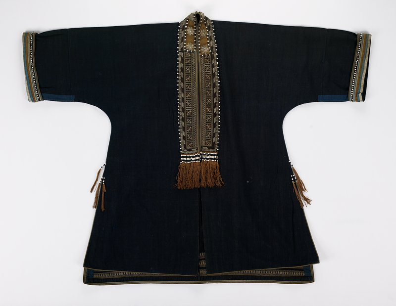 long, with slits at sides; blue with white, tan and blue trim; predominately brown cross-stitch around neck and front opening; white, tan, green and yellow embroidery at hem in back; trimmed with black and white beads and brown tassels; metal stars around neck