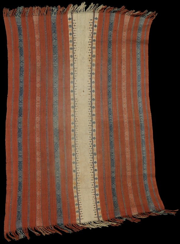 three strips sewn together; side pieces are rust with woven striped band and geometric bands in blue and cream; central cream section with small rust and blue geometric designs; twisted fringe on short ends