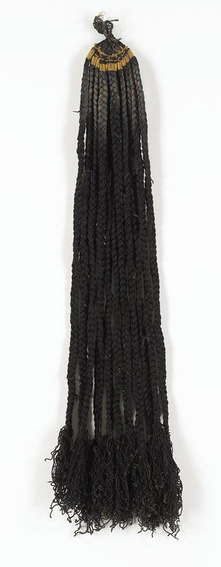"eleven strands of approximately 1/2"" black braids attached to top with tan ""binding""; piece of tape at top says ""173""; strands all have tassels"