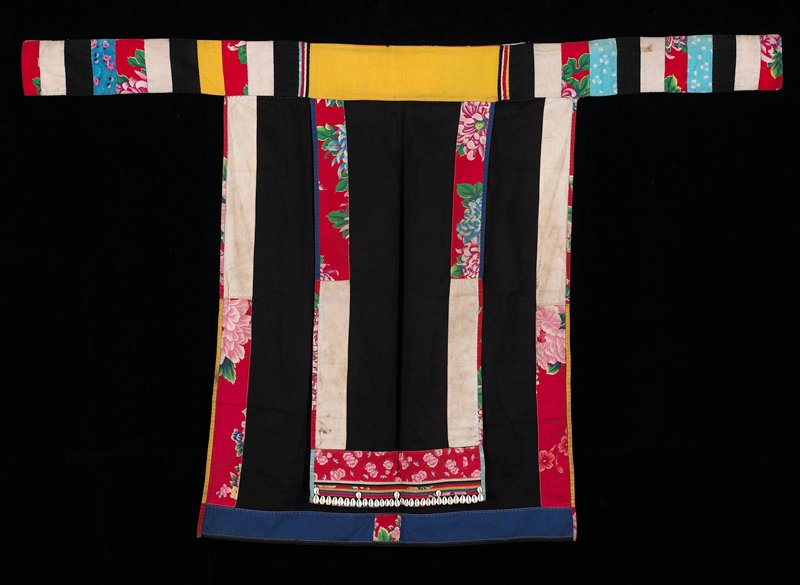 black with overapron; border of both sections and band are printed floral and plain fabrics in bright multicolors; bottom of overapron has bands of narrow applique trimmed with shells