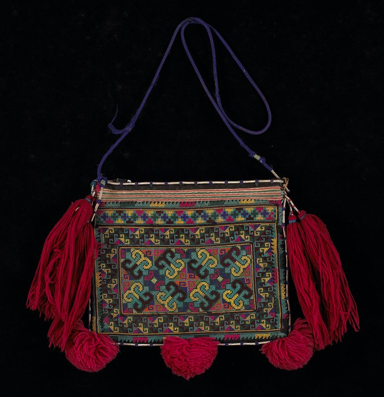 body is completely cross stitched geometric in greens and multicolor; top edge has narrow rows of applique with rows of metal springs, spaced in purple trim, around entire purse; purple strap; four red tassels, three pompoms; three zippers inside; blue lining