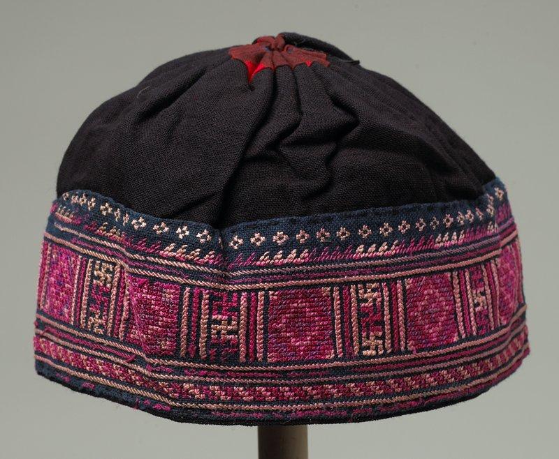 black skull cap; partially line; geometric cross stitch in reds and beige; horizontal design; uneven width around hat