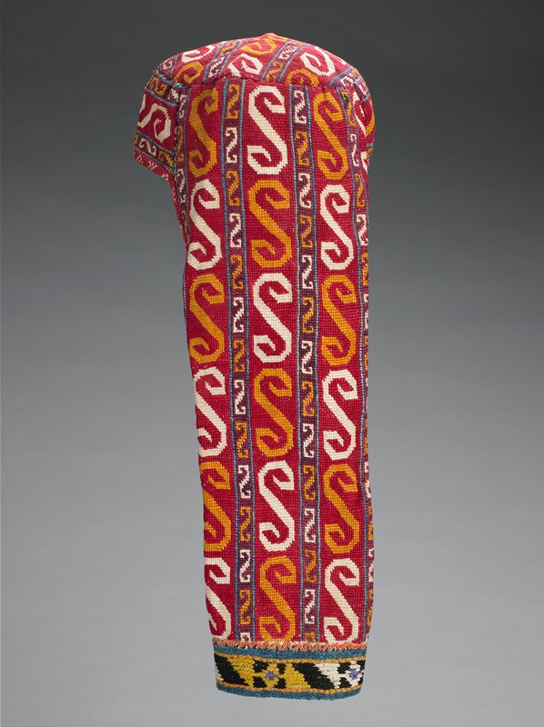 Embroidered band, warp-twined (LM) edge; Printed lining. Overall cross stitch embroidery on a cotton ground. The hat is constructed of three pieces: a circular crown, a band forming the front and sides, and a wide band extending down the back. There is an attached embroidered border at the bottom of the back band. The back band is partially lined with cotton fabric to draw the edges into a tube form. The crown is lined with silk/cotton ikat; a bull's-eye motif is centered in the crown. Embroidery is cross-stithed through a guaze-like striped fabric.
