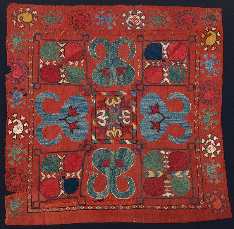 Hand woven red wool ground with polychrome wool and silk embroidery. There is no edge binding or backing. One edge is a selvage; the others are raw. The panel is hand stitched to black cotton fabric. The verso is not visible. May be folded under at top.