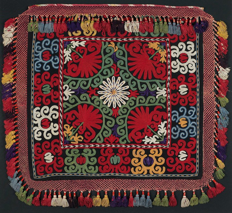 Braided-net fringe with tassels, cloth band. Black wool ground with polychrome silk embroidery. The edges are trimmed with a band of silk cross stitch embroidery on a cotton ground. There is an attached braided silk fringe with wrapped cotton and silk tassels. The embroidery is presently hand stitched to a fabric covered mount. the verso is not visible. Ikat strip at top.