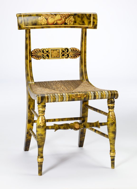 square seat of woven fibers; chair is painted in mostly gold, olive green, black; fruit and leaf design painted on chair back at top center; horizontal rail at middle of chair back has a star in a square design flanked by fan-like shapes; striped pattern at front of chair seat
