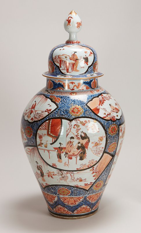 domed cover with spire finial painted with boys chasing a lion and with mother and child; vase has fan, lobed and leaf-shaped panels of figures in gardens and on terraces, some overlapping, reserved on blue scrolling foliate ground with scattered flower heads; neck has pomegranate and acanthus in a diaper border reserved with crustaceans
