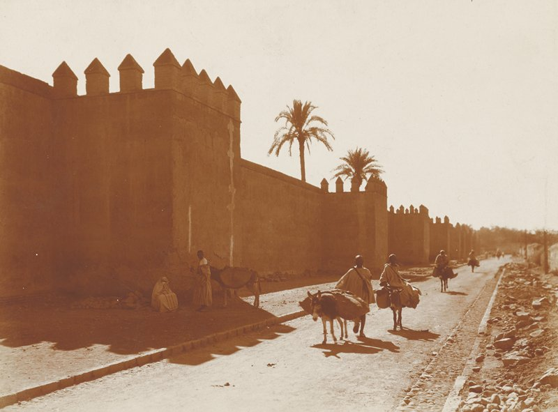 figures on a path, walking and riding on donkeys with packs; wall at L; man and woman rest in shade with donkey at L; Morocco