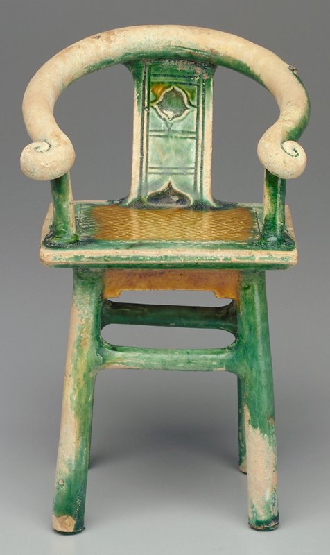 Tomb furniture; small horseshoe back chair; square seat with crosshatched pattern; incised decoration (organic elements and lines) on back; glazed tan and green