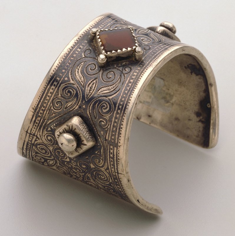 silver bracelet, two studs flanking diamond-shaped reddish gemstone at center; etched organic motif at upper surface; side metal rolled to form edge ends flat and wider than middle