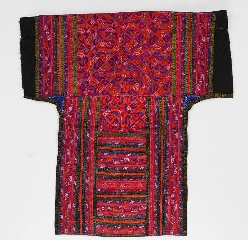 black lining; lower portion, center panel--geometric shapes embroidered on red background in blue, green and white, bordered in vertical embroidered bands and tapes; upper part--horizontal embroidered bands bordered by vertical embroidered bands; red dominant with white, blue, green