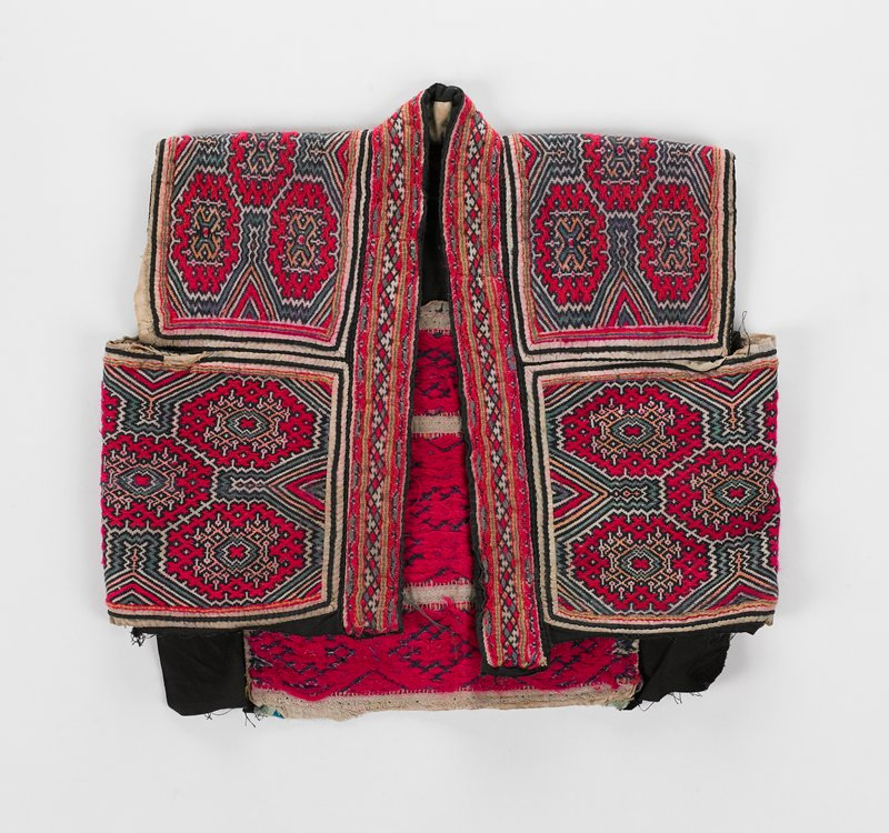 partial black lining; coarse geometric embroidered panels in maroon, black, green, pink bound in white and black tape borders and applied to black fabric; front and neck edge bound in wide embroidered tape--linear embroidered pattern