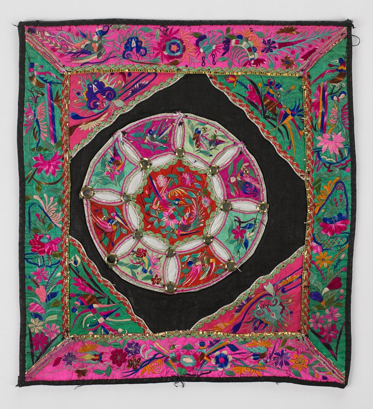 black cotton (linen?) center has circle of bird embroidered appliques in pink, green and orange linked together by metallic tape and metal mirror-like studs leaving see-through white petals; corner triangles and borders of green and pink are embroidered flowers, birds and masks; gold and silver metallic tape; black lining and piping
