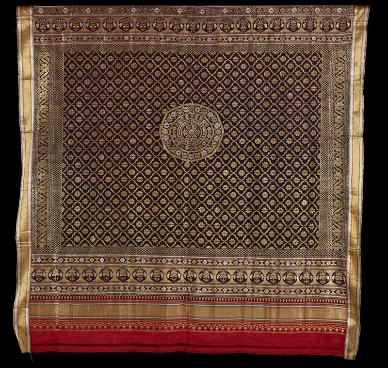 central area of purple loosely-woven field with overall design of gold and red flowers around central medallion; gold, silver, yellow, red floral and geometric borders; red end borders; netting sewn to back of side applied bands; brocaded
