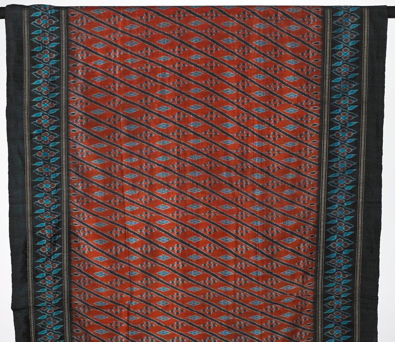 weft ikat, partially lined; orange/red central area with horizontal stripes, blue patterning; dark border with light blue and red designs
