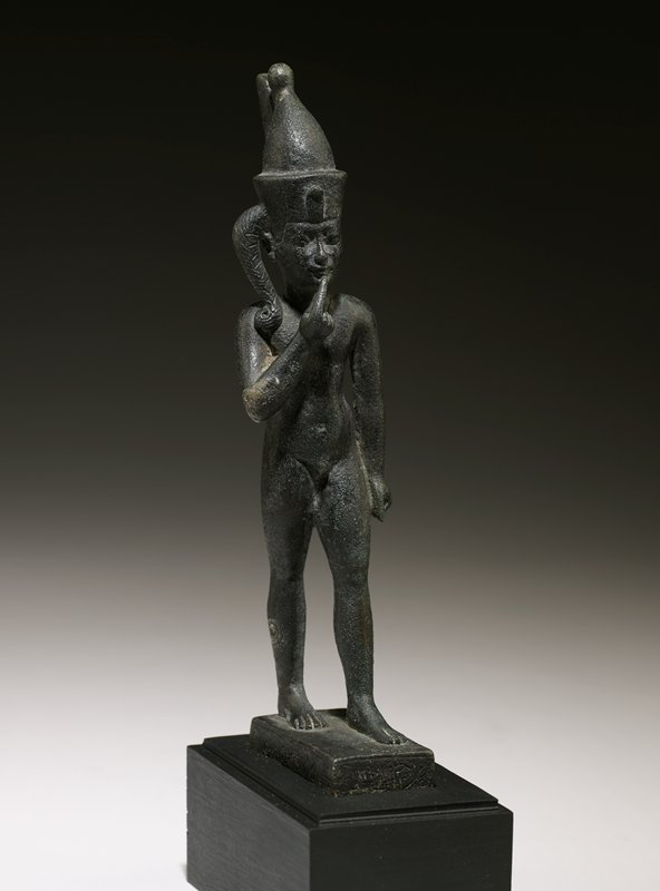 God Harsiesis, bronze, black, Egyptian, Ptolemaic; walking, right hand raised to chin, lock of hair over right ear, crowned with double crown of the two lands and uraeus, inscription on pedestal, figure nude, amulet suspended from neck,