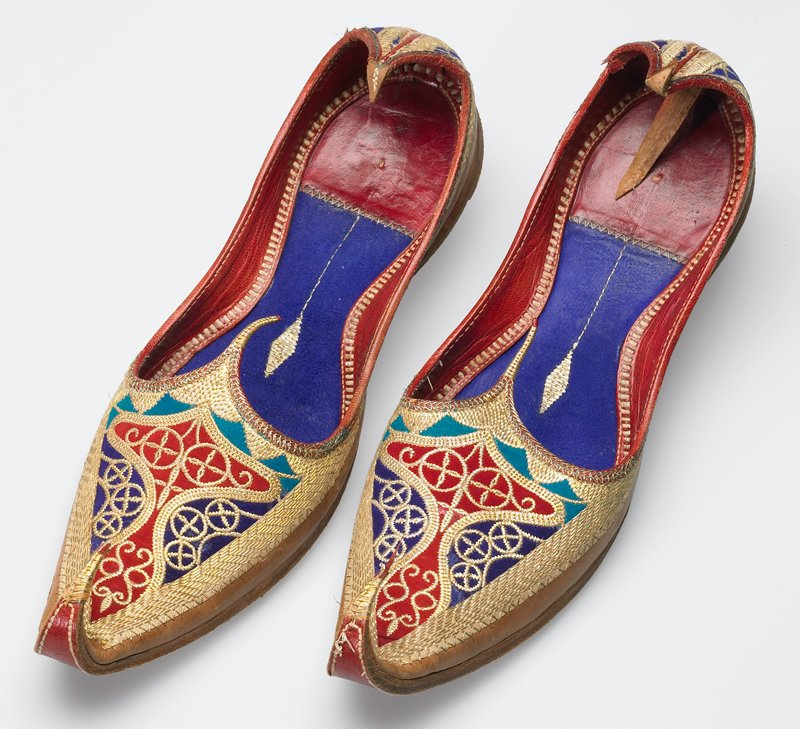 smooth tan leather pointed toe shoes with red leather and blue suede lining attached by cotton stitching; top of instep and back of heel heavily embroidered on red and blue suede with gold metallic thread
