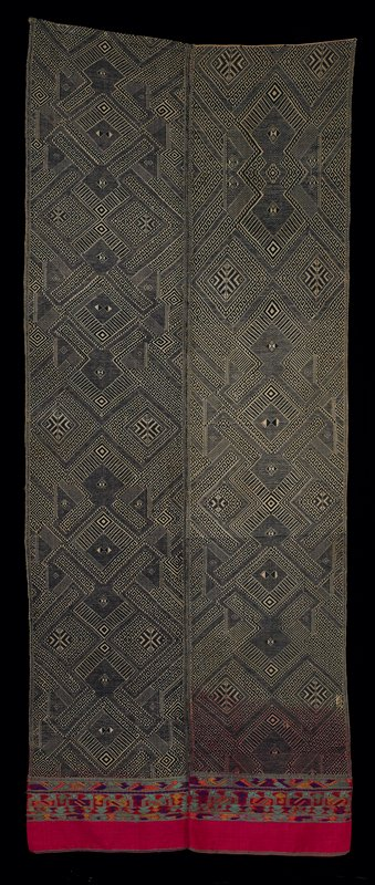 """two panels, indigo and natural, joined at selvedges; different but similar diagonal geometric patterns; 8"""" silk woven border at one end has narrow geometric rows of supplementary weft in red, purple, teal and orange; red silk warp continues into indigo panels, then changes"""