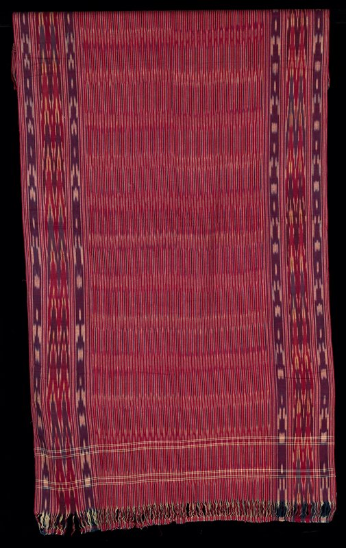 cotton ikat rectangle with fringe at two ends; center has small horizontal striped design with borders in a larger pattern; navy, burgundy and off-white
