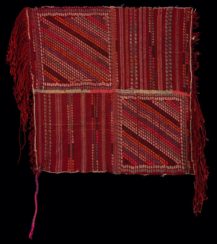 cotton label 158; two hand-sewn dark red woven panels, with diagonal multicolored embroidery on half and horizontal multicolored embroidery on other half of each panel; each panel has a short self fringe on one end and an attached long knotted fringe on other; one corner has braided tie