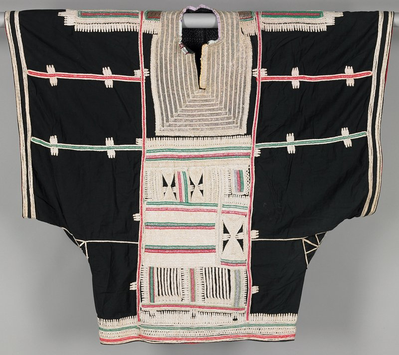 """wide black cotton dress with extra deep (26"""") sleeve holes; extremely ornate neck and bib of heavy wrapped metal; front and back panels, shoulders and bottom 4"""" are covered with applied white cotton braid with metallic strand; red and green trim and red facing on sleeves and bottom"""
